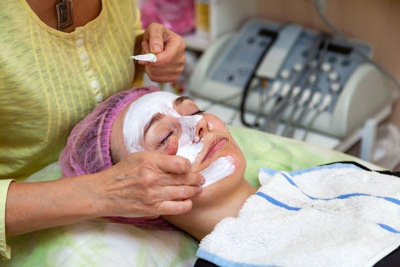 Ein erfahrener Cosmetologist wendet eine Maske der wei?en Creme auf dem Gesicht eines jungen M?dchens an, das auf der Couch w?hre stockfotografie