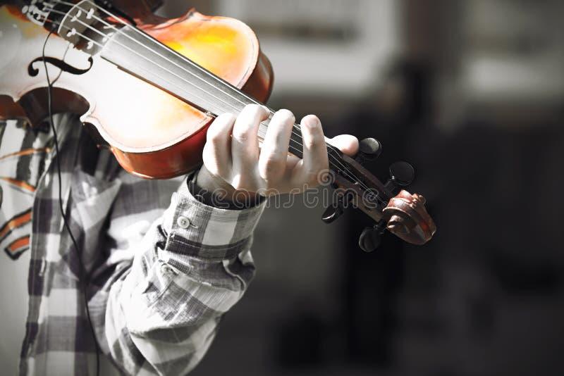 Ein erfahrener Violinist spielt eine Melodie auf einer alten schönen Violine lizenzfreie stockfotos
