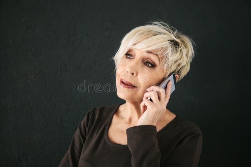 Ein erfolgreicher positiver älterer weiblicher Berater verhandelt über einen Handy Kommunikation zwischen der Leuteanwendung mode stockfotografie
