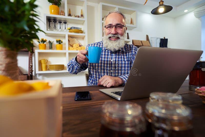 Ein erfreuter älterer Mann, der eine Tasse Tee bei der Anwendung des Laptops hält stockbilder