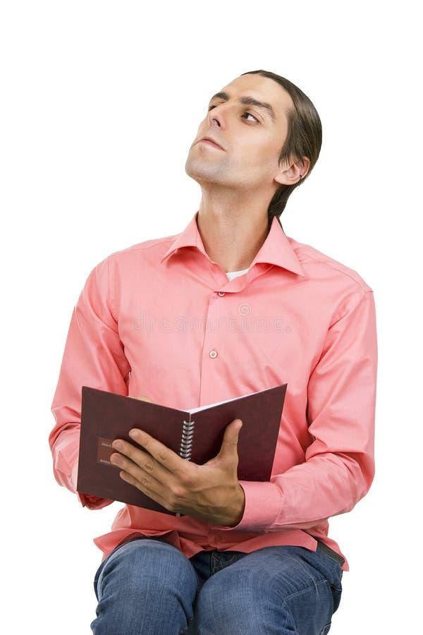 Ein ernster emotionaler junger Mann mit einem Notizblock (Notizbuch) stockfotos