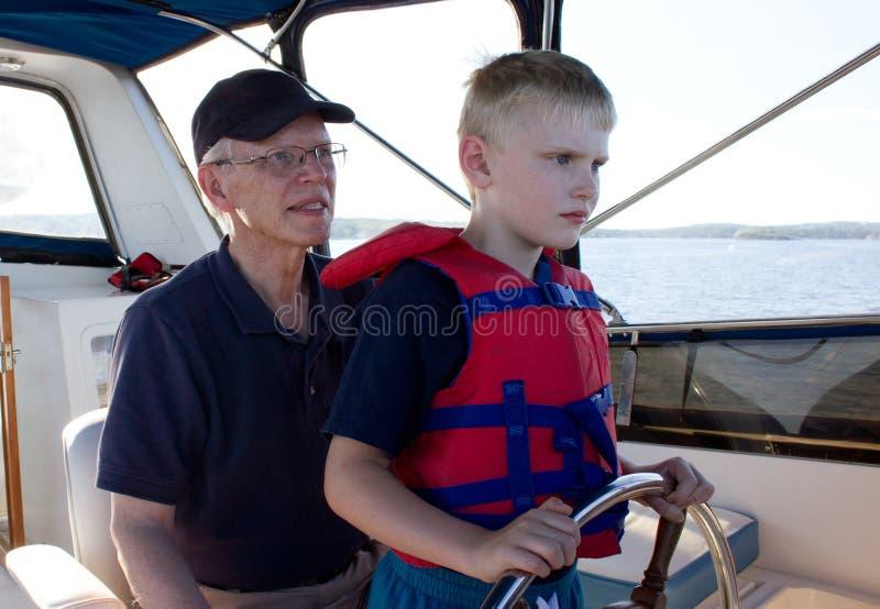 Ein ernstes Kind lernt Segeln von seinem Großvater stockbild