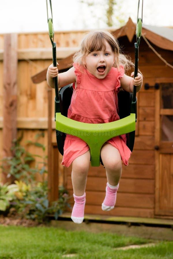 Ein erregbares junges lachendes Mädchen beim Spielen auf dem Schwingen lizenzfreies stockbild