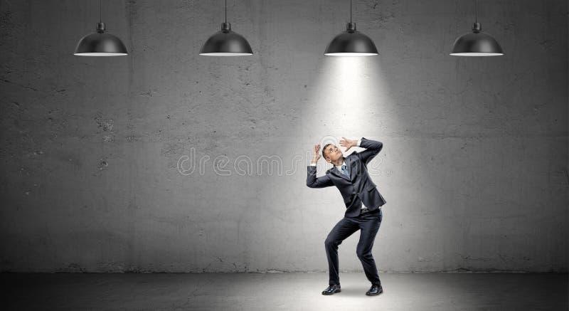 Ein erschrockener Geschäftsmann steht, kauernd unter die Strahlen von industriellen hängenden Lichtern nach rechts über ihm lizenzfreie stockfotos