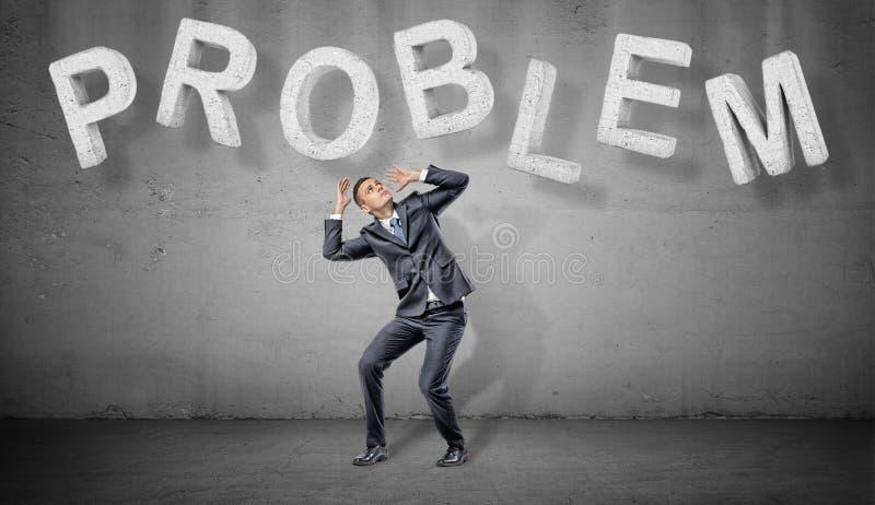 Ein erschrockener Geschäftsmann versteckt sich unter den großen konkreten Buchstaben, die ein Wort PROBLEM über ihm machen lizenzfreies stockbild