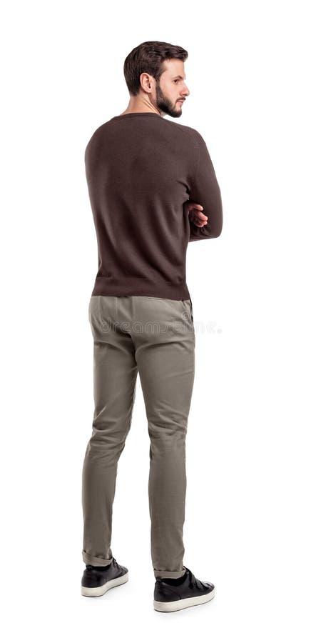 Ein erwachsener bärtiger Mann in den zufälligen Strickjackenständen zur Hälfte hinteres Ansicht drehte sich, um hinter seiner Sch stockbilder