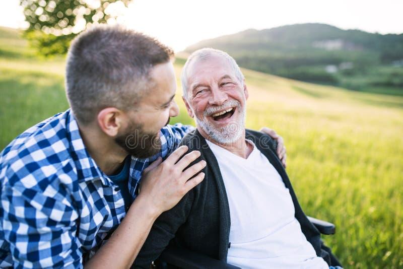 Ein erwachsener Hippie-Sohn mit älterem Vater im Rollstuhl auf einem Weg in der Natur bei dem Sonnenuntergang, lachend lizenzfreies stockbild