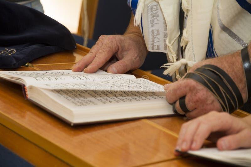 Ein erwachsener Mann, der auf eine Phrase in einem Bibelbuch sefer torah, beim Ablesen eines Betung zeigt stockbild