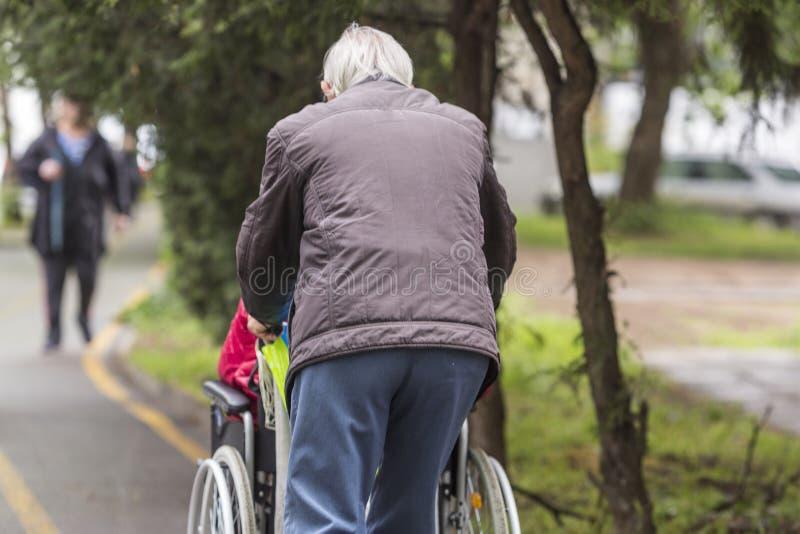 Ein erwachsener Mann, der einen Rollstuhl auf einem Fahrrad dr?ckt lizenzfreies stockfoto