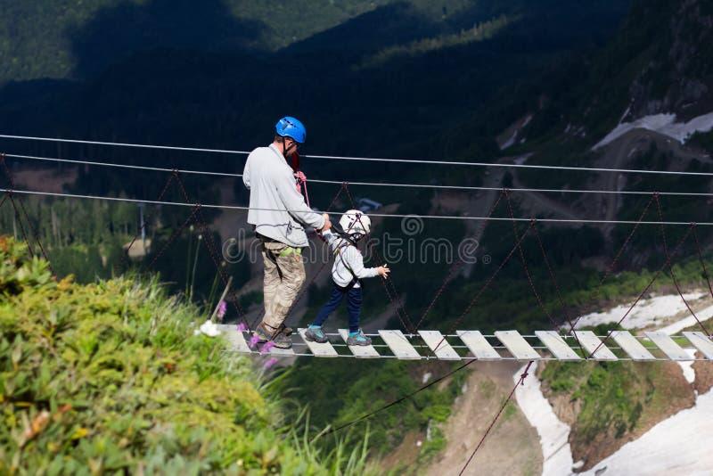 Ein erwachsener Mann und ein kleiner Junge in kletternden Gang auf einer extremen Brücke gehen stockfotos