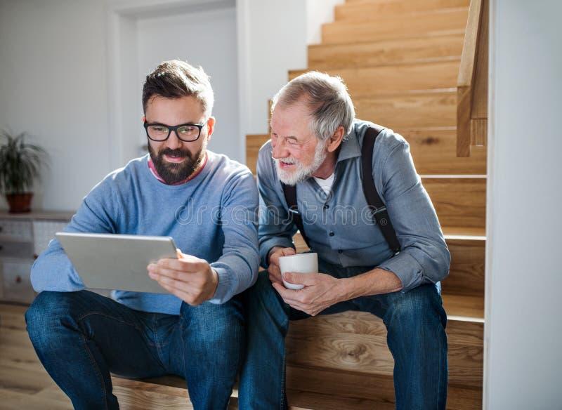 Ein erwachsener Sohn und ein älterer Vater mit der Tablette, die zuhause auf Treppe zu Hause sitzt lizenzfreies stockfoto