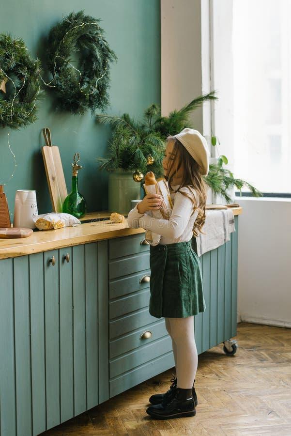 Ein fünfjähriges Mädchen in stilvollen Kleidern mit weißen und grünen Blumen hält eine Papiertüte mit einer Baguette in der Nähe  stockfotografie