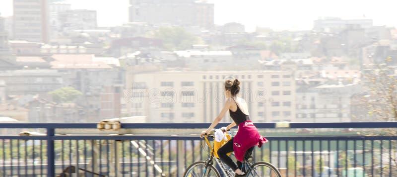 Ein Fahrrad der jungen Frau Reitauf Stadtstraßenbrücke mit undeutlichem hellem Stadtbildhintergrund lizenzfreie stockbilder