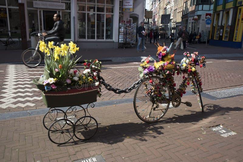 Ein Fahrrad mit einem Warenkorb, verziert mit künstlichen Blumen und einer Gummiente, die einen Souvenirladen annonciert stockfotografie