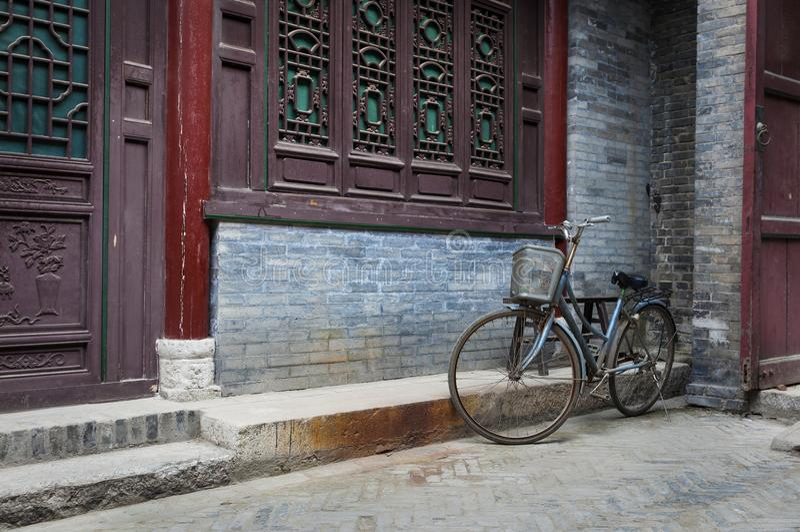 Ein Fahrrad parkte gegen eine verzierte Wand in der großen Moschee in der Stadt von Xian, China stockfotografie