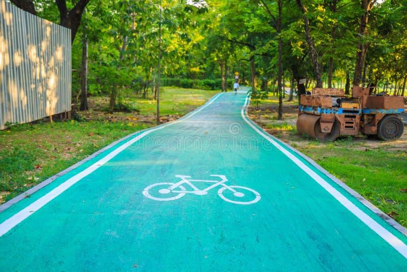 Ein Fahrradzeichen auf Radweg im Park mit Naturhintergrund lizenzfreie stockfotografie