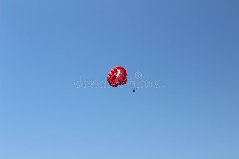 Ein Fallschirm mit einem Passagier, der in den Farben der türkischen Flagge für Parasailing gemalt wird, ist im Himmel hoch stockfoto