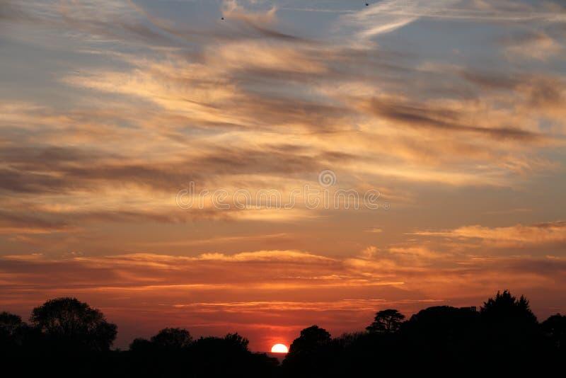 Ein fast eingestellter Sun in den bewölkten Himmeln lizenzfreies stockfoto