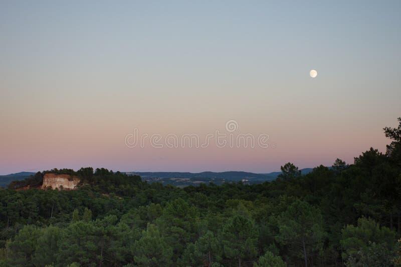 Ein fast Vollmond über den ockerhaltigen Klippen von Roussillon Frankreich lizenzfreie stockfotografie