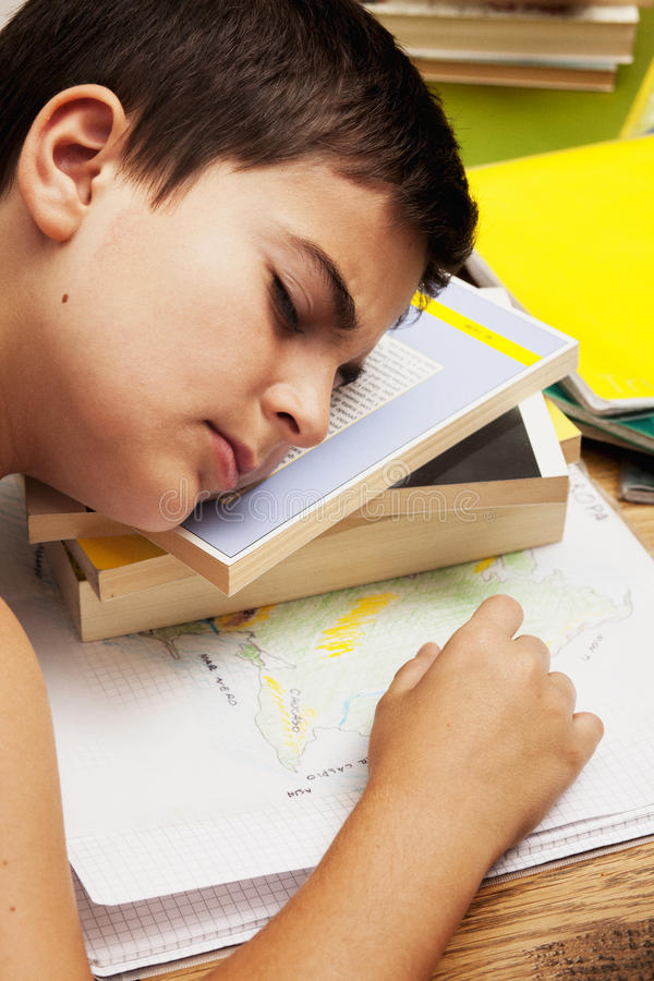 Ein fauler Junge, der auf dem Buch schläft lizenzfreies stockbild