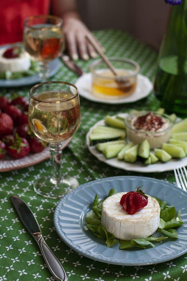 Ein Feinschmecker-Dinner für zwei Personen: gegrillte Camembert, Weißwein und verschiedene Vorspeisen lizenzfreie stockfotos