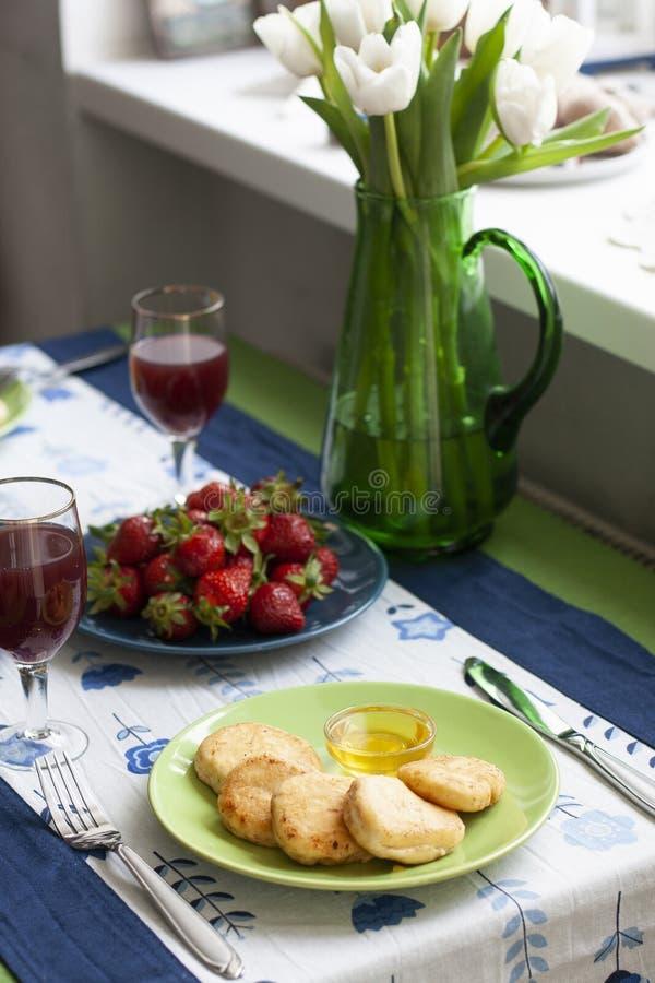 Ein feinschmeckerisches Frühstück für zwei: syrnyky, Erdbeeren, Traubensaft und Erdbeeren lizenzfreies stockfoto