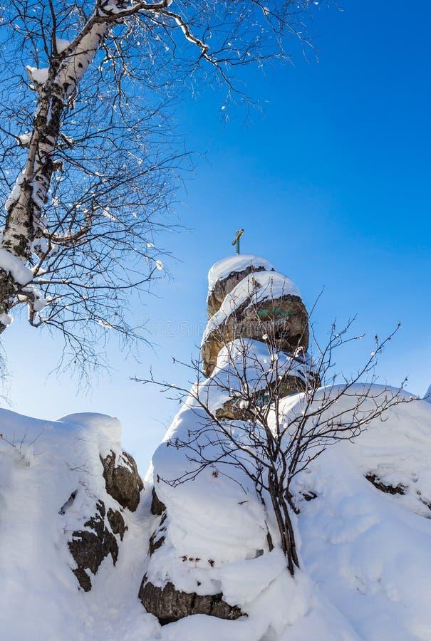 Ein Felsen mit einem orthodoxen Kreuz Gebirgskirche Erholungsort Belokurik lizenzfreies stockfoto