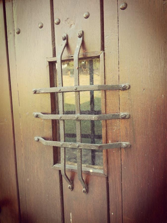 Ein Fenster mit Stangen auf der alten Holztür lizenzfreie stockbilder