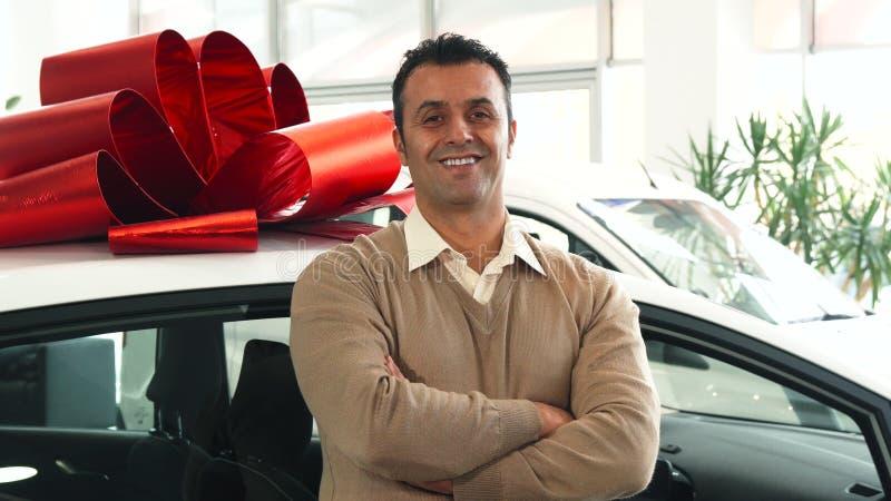 Ein fester Mann steht auf dem Hintergrund eines Autos mit einem Geschenkbogen stockfoto
