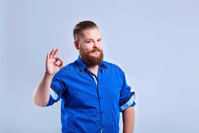 Ein fetter, bärtiger Mann zeigt ein Zeichen mit seinem Finger mit einem Eil lizenzfreie stockfotos