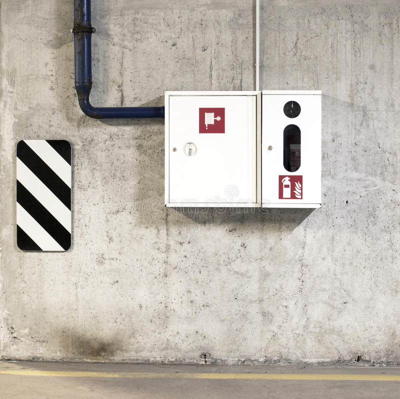 Ein Feuerlöscher und ein Feuerlöschschlauch im weißen Kasten auf der Wand stockfotografie
