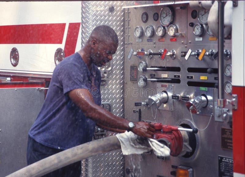 Ein Feuerwehrmann bearbeitet die Pumpen auf einem Löschfahrzeug lizenzfreie stockbilder