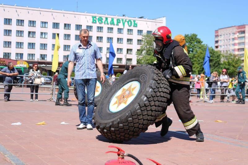 Ein Feuerwehrmann in einer feuerfesten Klage lässt laufen und dreht ein großes Gummi drehen herein einen Feuerbekämpfungswettbewe stockbilder