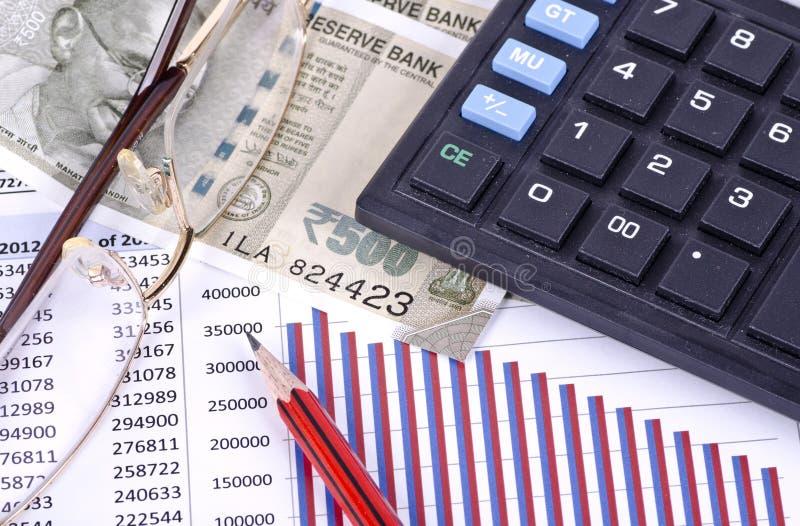Ein Finanzkreditbericht mit einem Bleistift, einem Taschenrechner, einem Geld und Gläsern lizenzfreie stockfotografie