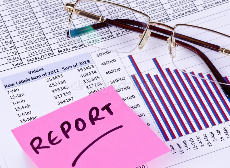 Ein Finanzkreditbericht mit Gläsern und einer klebrigen Anmerkung lizenzfreie stockbilder