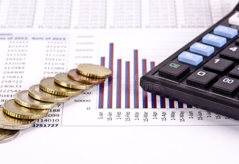 Ein Finanzkreditbericht mit Münzen und einem Taschenrechner lizenzfreies stockfoto