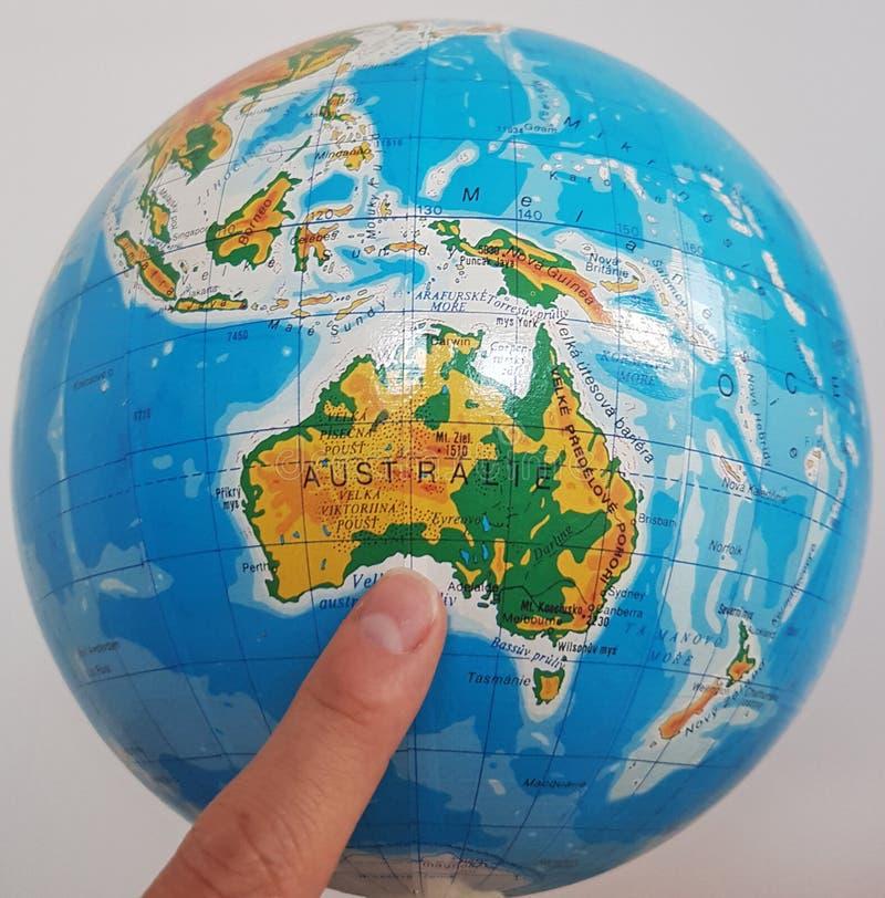 Ein Finger, der bei Australien auf einer Kugel zeigt lizenzfreies stockfoto