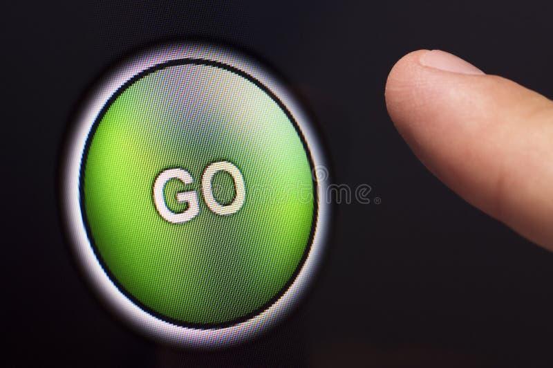 Der Finger, der ein Grün drückt, GEHEN Knopf auf mit Berührungseingabe Bildschirm stockbild