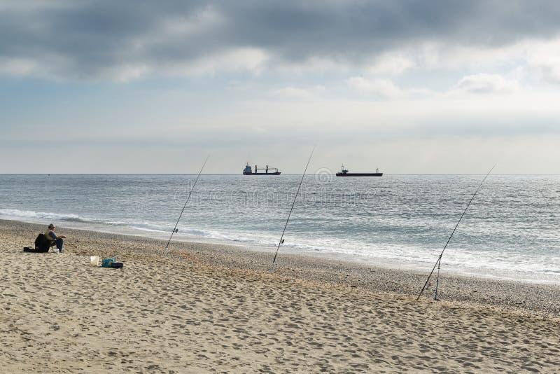 Ein Fischer, der auf dem Stuhl sitzt, beobachtet sein drei Angeln, das auf das Ufer in Position gebracht wird lizenzfreies stockbild