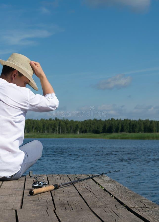 Ein Fischer mit einem Hut sitzt auf dem Pier des Flusses und der Blicke an der Angelrute an einem heißen sonnigen Tag lizenzfreies stockbild