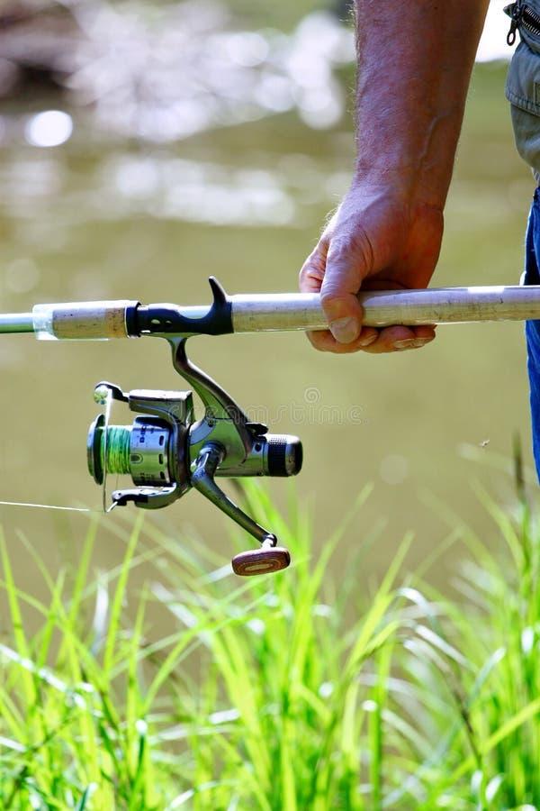 Ein Fischer mit einer Angelrute Nahaufnahme einer Hand, die spinnende Stange hält stockfotos