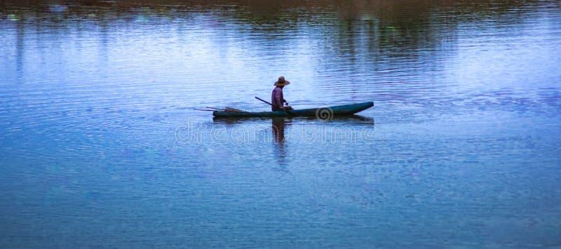 Ein Fischer sitzt auf dem kleinen Boot mitten in Fluss, lokale Landwirtschaft lizenzfreie stockfotos