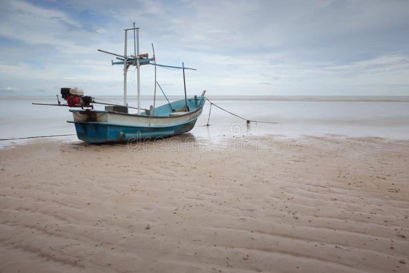 Ein Fischerboot auf einem Strand durch das Meer lizenzfreie stockfotos