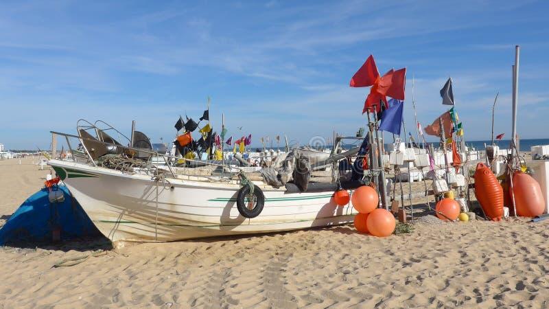 Fischerboot mit vielen Bojen auf dem langen, breiten, feinsandigen Strand von Montegordo, Algarve, Portugal royalty free stock image