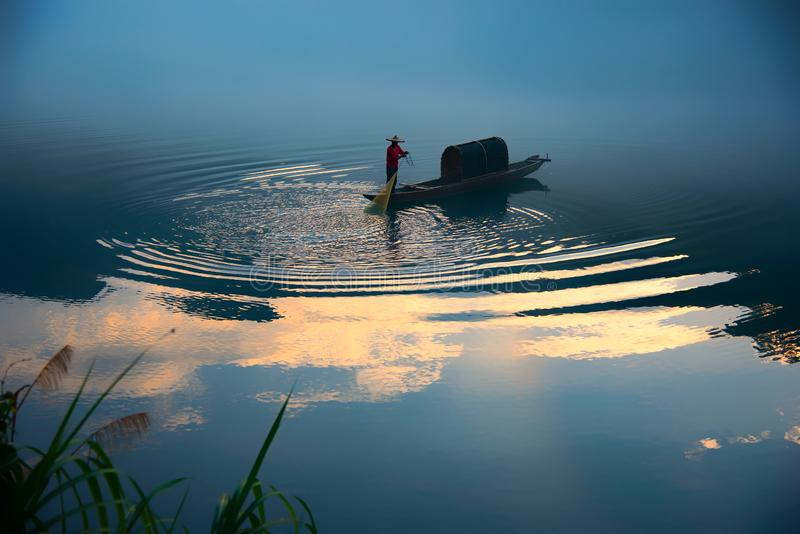 Ein fishman auf dem Boot im Nebel auf dem Fluss, die goldene Wolkenreflexion auf der Oberfläche von Fluss, gewordene goldene Kräu stockfotografie