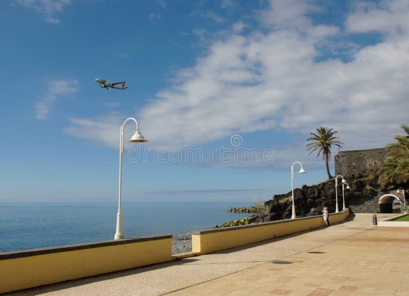 Ein Fliegenflugzeug im Himmel und im schönen Meerblick von Madeira lizenzfreies stockfoto
