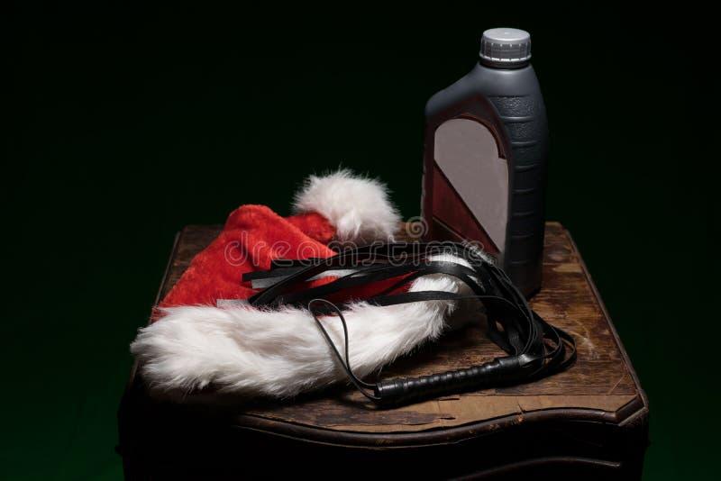 Ein flockiger roter und weißer Sankt-Hut, eine schwarze Peitsche und eine Flasche Motorenöl, auf einem alten wodden die Tabelle u stockfoto