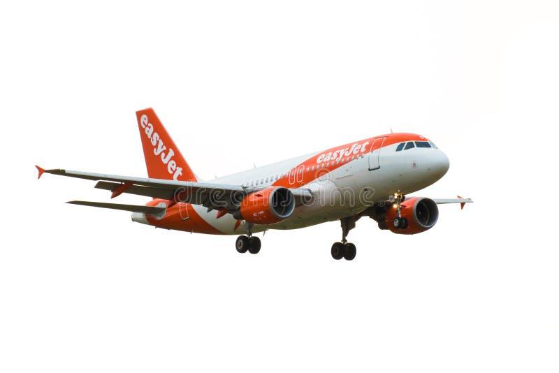 Ein Flugzeug easyJet Fluglinien-Airbusses A319-100 kommt herein, an Flughafen Londons Gatwick zu landen Getrennt auf einem weißen lizenzfreie stockfotos