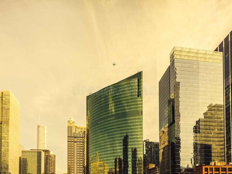 Ein Flugzeug fliegt über moderne Architektur entlang Wacker-Antrieb bei Wolf Point in Chicago Städtisches Stadtbild lizenzfreie stockfotografie