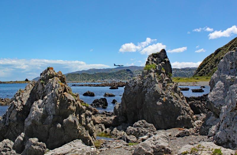 Ein Flugzeug macht es ist Endanflug zu Wellington Airport über der schroffen Küste des Kochs Straits lizenzfreie stockfotos